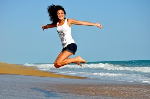 Happy girl jumping on beach