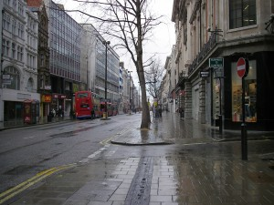 Rainy London street with red bus